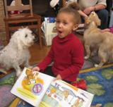 Photo of Willie the dog listening to a little girl read at the library