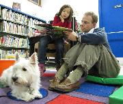 Photo of Pablo the dog reading with a family at the library