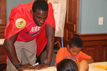 """Jeff Green assists Steele Downing with his superhero Friday at the Petworth Neighborhood Library's """"Create Your Own Superhero Wo"""