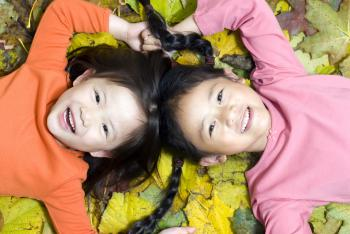 two girls on fall leaves