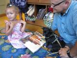 Photo of Ava the dog reading with a girl at the library