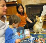 Photo of Bailey the dog reading with a family at the library