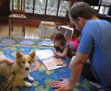 Photo of Bailey the dog reading with a girl and her dad at the library