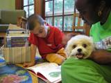 Photo of Brad the dog reading with a boy at the library