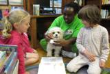 Photo of Brad the dog with some girls at the library