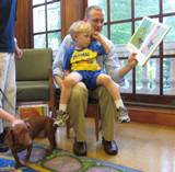 Photo of Buddy the dog reading with a family at the library