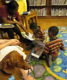 Photo of Buddy the dog and twin boys reading at the library