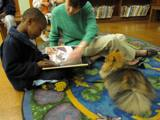 Photo of Chance the dog reading with a boy at the library
