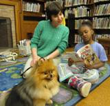 Photo of Chance the dog reading with a little girl