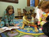 Photo of Dakota the dog reading with a girl at the library
