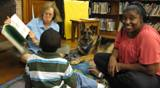 Photo of Dakota the dog listening to a family read at the library
