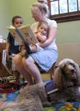 Photo of Ella the dog listening to a family read at the library