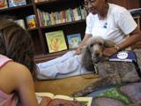 Photo of Ella the dog reading with a girl at the library