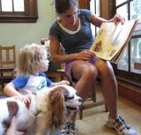Photo of Fenway the dog reading with a family at the library