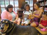 Photo of Freddie the dog and a family reading at the library