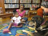 Photo of Freddie the dog reading with a girl at the library