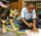 Photo of Freddie listening to a boy read at the library