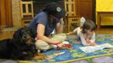 Photo of Happy the dog reading with another girl at the library