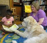 Photo of Harpo the dog and a girl reading