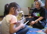 Photo of Harpo the dog reading with a girl at the library