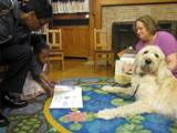Photo of Harpo the dog and a family reading at the library