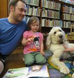 Photo of Harpo the dog and a family at the library