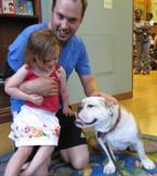 Photo of Honey the dog and a girl at the library
