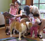 Photo of Honey the dog and a family at the library