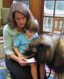 Photo of Kazzy the dog reading with a boy at the library