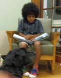 Photo of Kirby reading with a boy at the library
