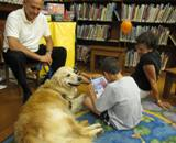 Photo of Leo the dog reading with a boy at the library