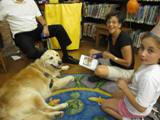 Photo of Leo the dog reading with a girl at the library