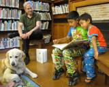 Leo the dog reading with boys at the library
