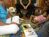 Photo of Leo the dog and a family reading and relaxing at the library