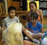 Photo of Leo the dog and a family at the library