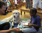 Photo of Leo the dog and a girl reading at the library