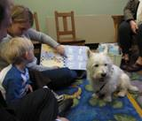 Photo of Pablo the dog reading with a family