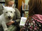 Photo of Pablo the dog reading with a girl