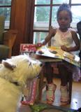 Photo of Pablo the dog reading with a girl at the library