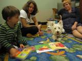 Photo of Pablo the dog and a family reading at the library