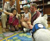 Photo of Pablo the dog listening to a family read at the library