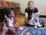 Photo of Pup-A-Roo the dog reading with a girl at the library