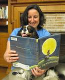 Photo of Quincy the dog enjoying a book at the library