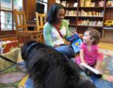 Photo of Teddy the dog reading with a family at the library