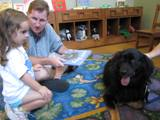 Photo of Teddy the doggie and a family reading at the library
