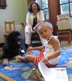Photo of Teddy the doggie and girl reading at the library