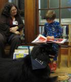 Photo of Teddy the dog listening to a boy read