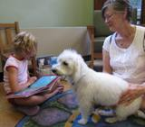 Photo of Willie the dog and a girl reading at the library
