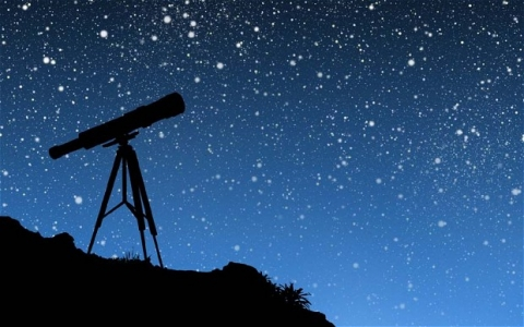Image is the silhouette of a telescope against a backdrop of a vivid night sky filled with stars.