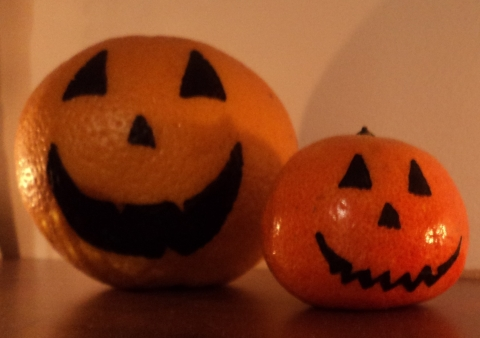 Image of clementines decorated as jack-o-lanterns!